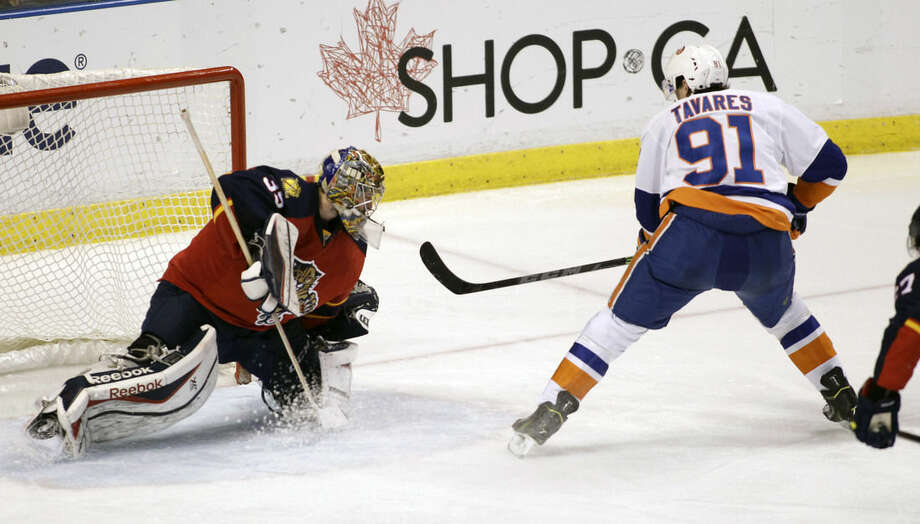 New York Islanders' John Tavares (91) scores a goal on Florida Panthers goalie Dan Ellis during the second period of an NHL hockey game, Saturday, March 7, 2015, in Sunrise, Fla. (AP Photo/Luis M. Alvarez)