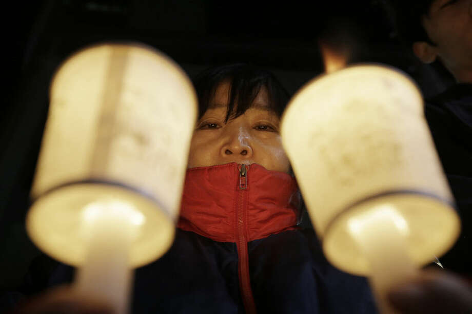 A South Korean conservative activist holds candles during a rally to wish the U.S. Ambassador to South Korea Mark Lippert a speedy recovery in front of Severance hospital in Seoul, South Korea, Friday, March 6, 2015. Police on Friday investigated the motive of the anti-U.S. activist they say slashed Lippert, as questions turned to whether security was neglected. (AP Photo/Ahn Young-joon)