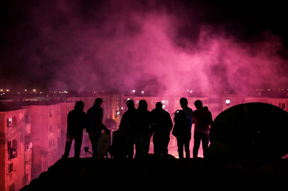 "In this Thursday, March 5, 2015 photo, young men observe from a rooftop as smoke from flares fills the sky during a local wedding in Salam City, a suburb on the outskirts of Cairo. Since the 2011 uprising, the music of ""Mahraganat,"" Arabic for ""festivals,"" has emerged from and spread through impoverished communities, where local musicians play, especially during weddings, their auto-tuned beats and songs that tackle social, political and cultural issues. (AP Photo/Mosa'ab Elshamy)"