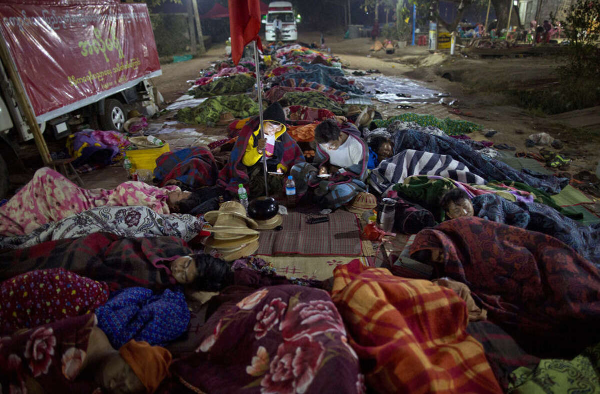 Students protesters who have been staging a sit-in since March 3, lie on the ground covered in blankets as two-others check their mobile phones in Letpadan, 140 kilometers (90 miles) north of the country's main city Yangon, Myanmar, at the dawn of Saturday March 7, 2015. On Friday, March 6 in another location in Letpadan police cracked down on student protesters opposing Myanmar's new education law, roughly grabbing demonstrators and loading them onto trucks in the third such clampdown in as many days. More protests were held on later on Friday in solidarity with the protesting students and condemning the crackdowns in other towns in Myanmar. (AP Photo/Gemunu Amarasinghe)