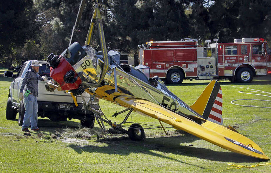 The World War II-era trainer airplane that actor Harrison Ford crash-landed Thursday is removed from Penmar Golf Course in the Venice area of Los Angeles, Friday, March 6, 2015. Ford is hospitalized with undisclosed injuries that his publicist says are not life-threatening. The actor was flying the plane when it lost engine power shortly after takeoff from nearby Santa Monica, Calif., Municipal Airport. No one on the ground was hurt. (AP Photo/Nick Ut)