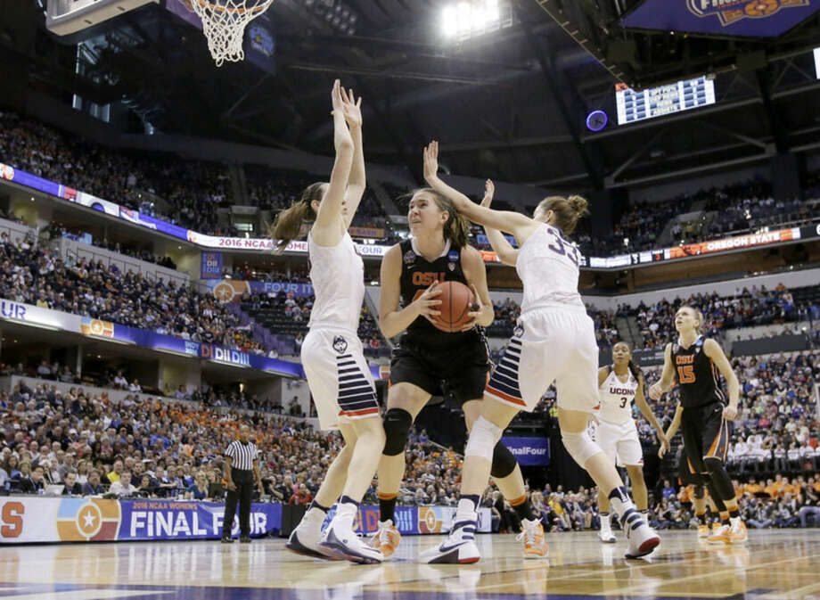 Oregon State's Ruth Hamblin (44) puts up a shot against Connecticut's Breanna Stewart (30) and Katie Lou Samuelson (33) during the first half of a national semifinal game at the women's Final Four in the NCAA college basketball tournament Sunday, April 3, 2016, in Indianapolis. (AP Photo/AJ Mast)