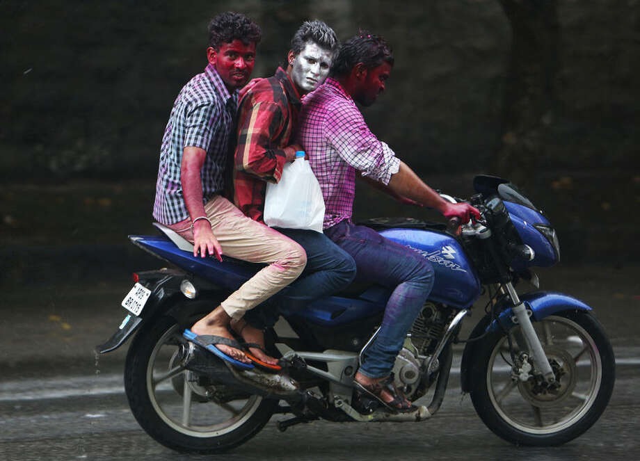 Indian men, their faces smeared with colored powder, ride a motorbike on Holi the Hindu festival of colors, in Hyderabad, India, Friday, March 6, 2015. Holi also marks the advent of spring. (AP Photo/Mahesh Kumar A.)