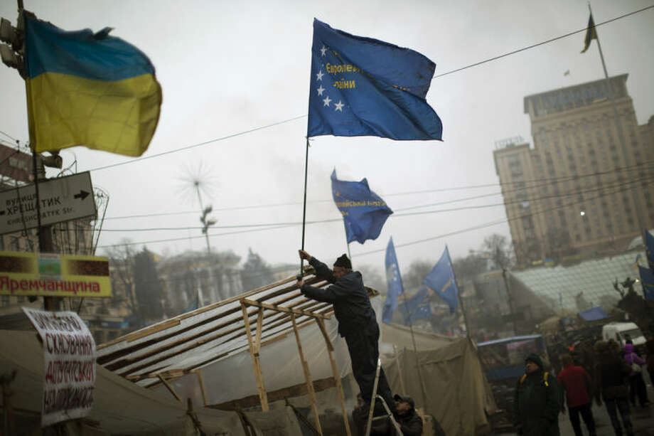 An anti-Yanukovych protester sets an European Union flag on top of a tent in Kiev's Independence Square, the epicenter of the country's current unrest, Ukraine, Sunday, March 2, 2014. A convoy of hundreds of Russian troops is heading toward the regional capital, Simferopol on the Crimean peninsula in Ukraine today. On the road from Sevastopol, the Crimean port where Russia maintains a naval base, AP journalists saw 12 military trucks. Russian troops took over the strategic Black Sea peninsula yesterday and are ignoring international protests. (AP Photo/Emilio Morenatti)