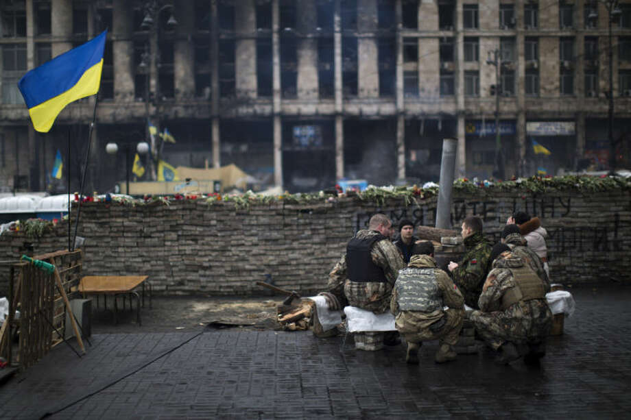 Anti-Yanukovych protesters warm themselves next to a fire as they guard one of the entrance in Kiev's Independence Square, the epicenter of the country's current unrest, Ukraine, Sunday, March 2, 2014. A convoy of hundreds of Russian troops is heading toward the regional capital, Simferopol on the Crimean peninsula in Ukraine today. On the road from Sevastopol, the Crimean port where Russia maintains a naval base, AP journalists saw 12 military trucks. Russian troops took over the strategic Black Sea peninsula yesterday and are ignoring international protests. (AP Photo/Emilio Morenatti)