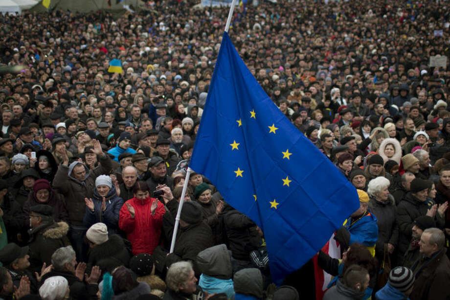 AP photo / Emilio MorenattiPeople applaud as the European Union flag held by a protester arrives at the Independence square during a rally in Kiev Ukraine, Sunday.