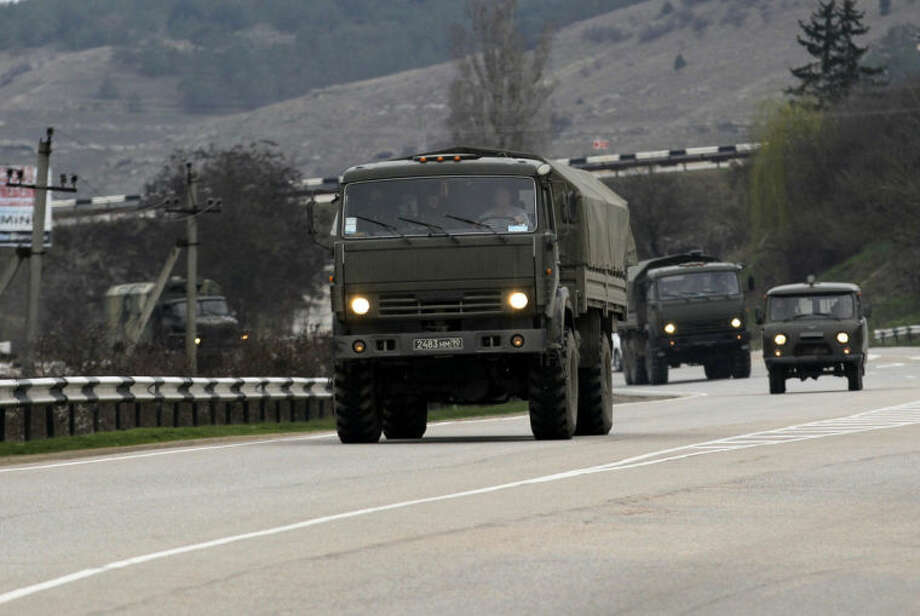 A Russian convoy moves from Sevastopol to Sinferopol in the Crimea, Ukraine, Sunday, March 2, 2014. A convoy of hundreds of Russian troops headed toward the regional capital of Ukraine's Crimea region on Sunday, a day after Russia's forces took over the strategic Black Sea peninsula without firing a shot. The new government in Kiev has been powerless to react. Ukraine's parliament was meeting Sunday in a closed session. (AP Photo/Darko Vojinovic)