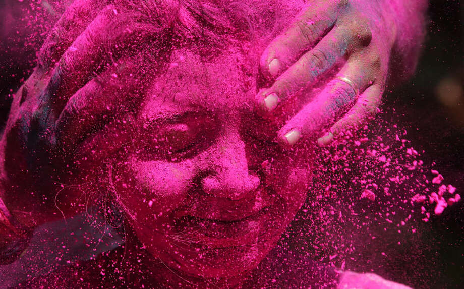 An Indian woman shuts her eyes as coloured powder is smeared on her face during celebrations marking Holi, the Hindu festival of colors, in Mumbai, India, Friday, March 6, 2015. Holi, India's joyful and colorful celebration of the arrival of spring along with several religious myths and legends, has long ago ceased to be only a Hindu festival. The streets and lanes across most of India turn into a large playground where people off all faiths throw colored powder and water at each other. (AP Photo/Rajanish Kakade)