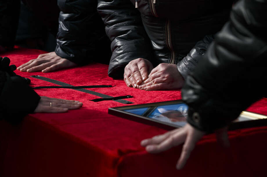 Relatives touch the coffin of a miner killed in an explosion on Wednesday at more than 1,000 meters (3,200 feet) underground at the Zasyadko mine, in Donetsk, Ukraine, Friday, March 6, 2015. Officials in a separatist rebel-held city in east Ukraine say the death toll from an accidental explosion at a coal mine has risen to 33.(AP Photo/Vadim Ghirda)