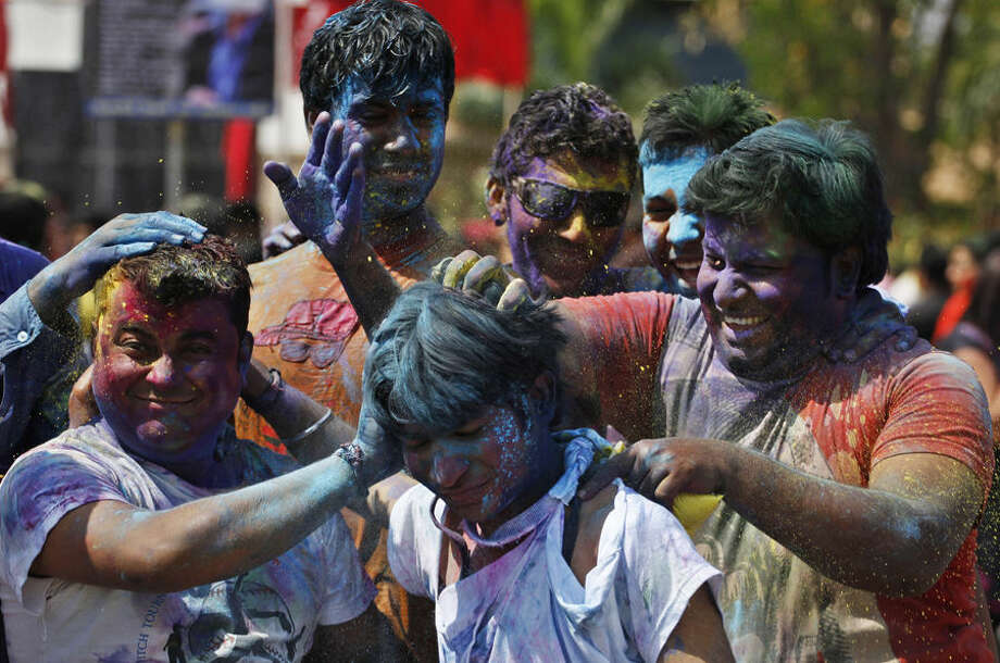 Indian boys smear coloured powder on another as they celebrate Holi, the Hindu festival of colors, in Ahmadabad, India, Friday, March 6, 2015. Holi also marks the advent of spring. (AP Photo/Ajit Solanki)