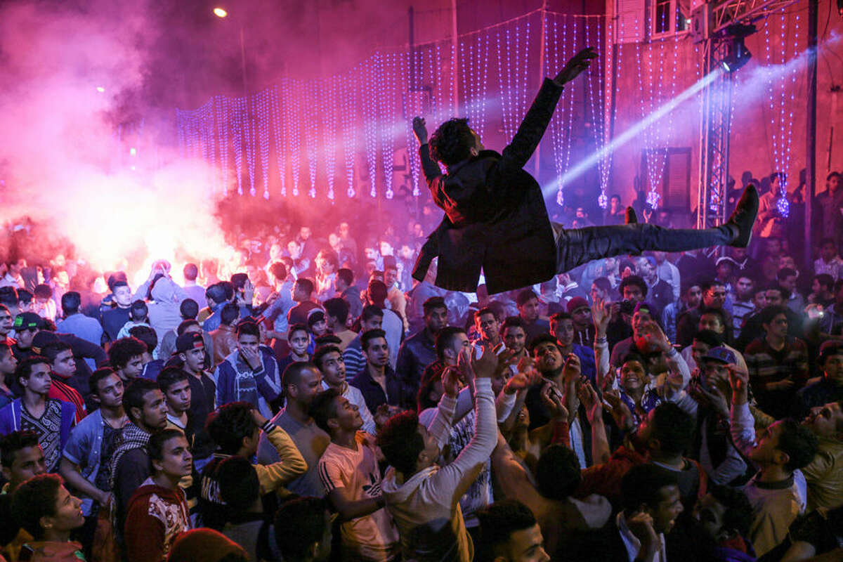 """In this Thursday, March 5, 2015 photo, youth dance at a local wedding in Salam City, a suburb on the outskirts of Cairo. Since the 2011 uprising, the music of """"Mahraganat,"""" Arabic for """"festivals,"""" has emerged from and spread through impoverished communities, where local musicians play, especially during weddings, their auto-tuned beats and songs that tackle social, political and cultural issues. (AP Photo/Mosa'ab Elshamy)"""