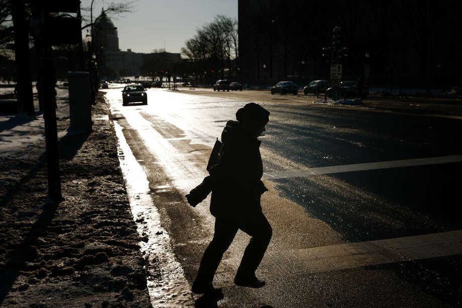 The Capitol Dome is visible as a woman crosses Pennsylvania Avenue in the cold in Washington, Friday, March 6, 2015. Low temperatures and snow that hit the region Thursday at the tail end of a brutal winter were expected to continue to affect the Mid-Atlantic region into Friday. The National Weather Service says the system is then expected to pull well out into the Atlantic Ocean. (AP Photo/Andrew Harnik)