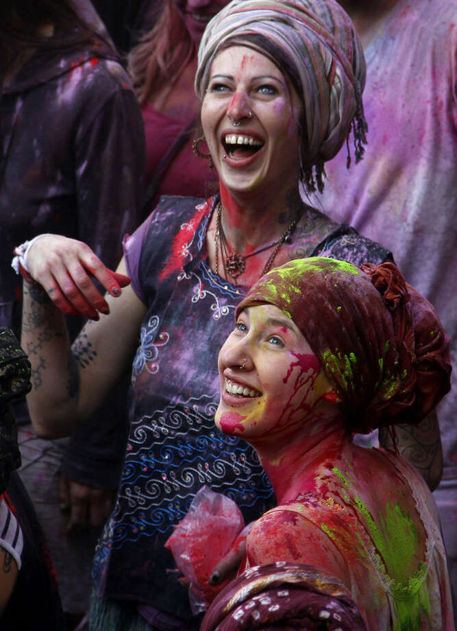 Foreign tourists, their faces smeared with coloured powder, join in celebrations marking Holi in Pushkar, India, Friday, March 6, 2015. Holi, India's joyful and colorful celebration of the arrival of spring along with several religious myths and legends, has long ago ceased to be only a Hindu festival. The streets and lanes across most of India turn into a large playground where people off all faiths throw colored powder and water at each other. (AP Photo/ Deepak Sharma)