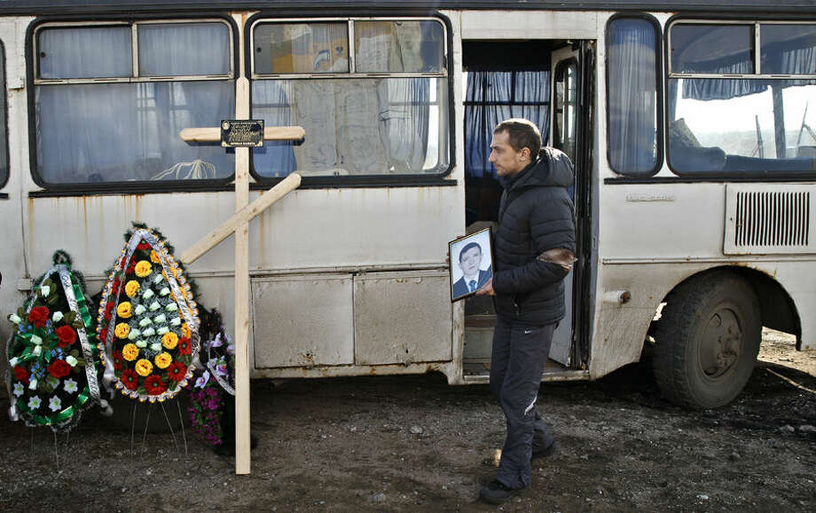 A man holds the picture of a miner killed in an explosion on Wednesday at more than 1,000 meters (3,200 feet) underground at the Zasyadko mine, during a funeral for the victims of the accident in Donetsk, Ukraine, Friday, March 6, 2015. Tens of miners died in the accident. (AP Photo/Vadim Ghirda)