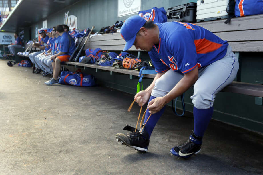 New York Mets pitcher Daisuke Matsuzaka ties his shoe before starting an exhibition spring training baseball game against the St. Louis Cardinals Sunday, March 2, 2014, in Jupiter, Fla. Matsuzaka allowed one run and two hits in two innings of work in the Mets' 7-1 loss to the Cardinals. (AP Photo/Jeff Roberson)