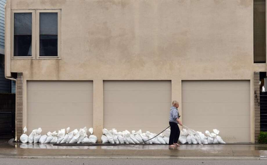 A resident hoses off a neighbor's driveway along Ocean Boulevard between 66th and 72nd Place, in Long Beach, Calif., Sunday, March 2, 2014. Flooding occurred when heavy surf eroded the protective sand berm Saturday night, resulting in 20 homes on Ocean Blvd between 66th and 72nd Place, sustaining damage to either living levels or parking areas. No residents were reported to be displaced, said Long Beach Fire Department Public information Officer Will Nash. (AP Photo/Daily Breeze, Stephen Carr)
