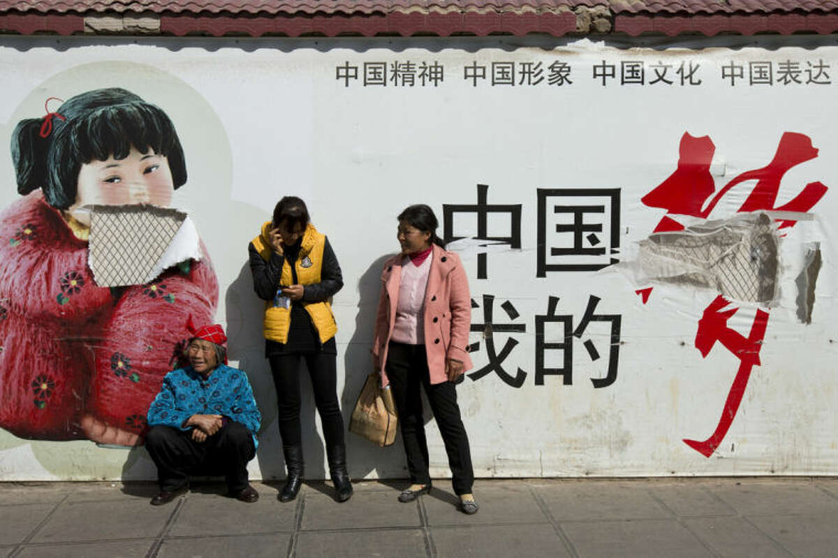 """Passengers wait in front of a broken propaganda poster featuring """"the China Dream"""" outside the Kunming Railway Station in Kunming, in western China's Yunnan province, Sunday, March 2, 2014. More than 10 assailants slashed scores of people with knives at the train station in southern China in what officials said was a terrorist assault by ethnic separatists from the far west. Twenty-nine slash victims and four attackers were killed and 143 people wounded. (AP Photo/Alexander F. Yuan)"""