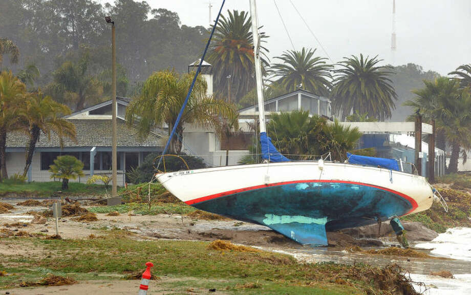 A sailboat washed ashore near a restaurant at Goleta, Calif., Saturday, March 1, 2014. The storm marked a sharp departure from many months of drought that has grown to crisis proportions for the state's vast farming industry. However, such storms would have to become common to make serious inroads against the drought, weather forecasters have said. (AP Photo/The News-Press, Mike Eliason)