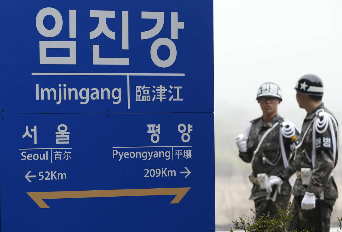 South Korean soldiers walk by a signboard showing the distance to the North Korea's capital Pyongyang and to South Korea's capital Seoul from Imjingang Station near the border village of the Panmunjom in Paju, South Korea, Saturday, April 9, 2016. North Korea said Saturday it has successfully tested a new intercontinental ballistic rocket engine that will give it the ability to stage nuclear strikes on the United States. (AP Photo/Lee Jin-man)