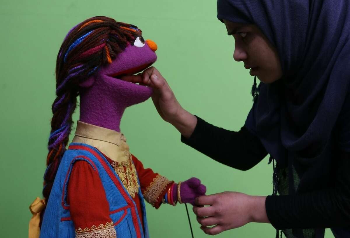 In this Thursday, April 7, 2016 photo, Razia, an Afghan puppet caretaker, right, cleans Sesame Street's new character, a sassy, fun 6-year-old Afghan girl called Zari, after a recording session for her first appearance on the local production of Sesame Street, called Baghch-e-Simsim in Kabul. She joins Sesame Street's multi-cultural line-up, which includes Muppets in Bangladesh, Egypt and India who each do separate segments on their own national programs. (AP Photo/Rahmat Gul)
