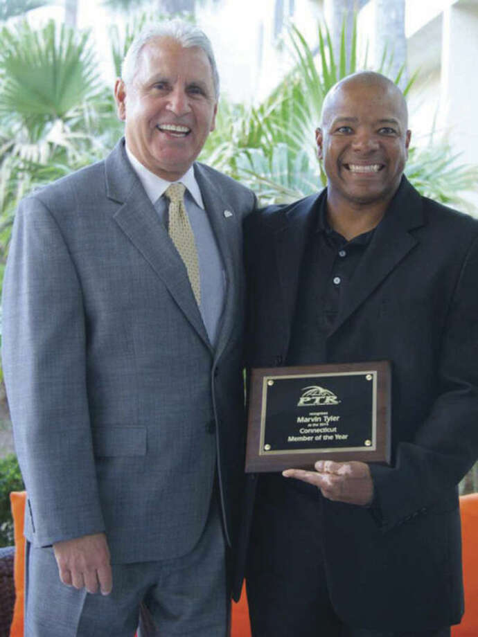Contributed photoMarvin Tyler (right) of Norwalk displays the plaque he received after being named the Professional Tennis Registry Member of the Year for the state of Connecticut last week in Hilton Head Island, S.C. Pictured with Tyler is PTR Board President Jorge Andrew.