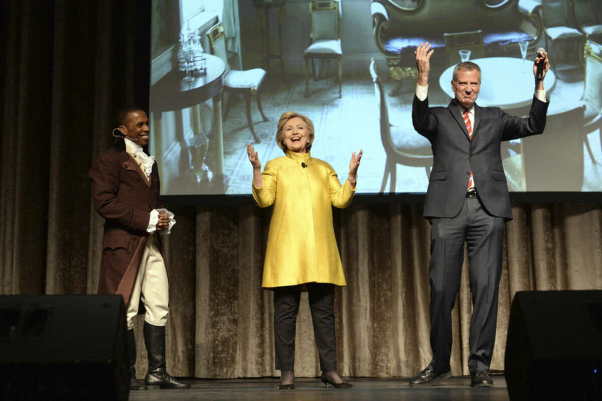 """FILE - In this April 9, 2016 file photo, Leslie Odum Jr., left, from the Broadway musical """"Hamilton,"""" presidential candidate Hillary Clinton, center, and New York City Mayor Bill de Blasio, right, perform at the 94th annual Inner Circle Dinner in New York. Clinton and de Blasio have come under fire over their comedy skit at the show that some people feel was racially insensitive. Many in the room where it happened, which was filled with New York politicians, power brokers and reporters, laughed at the joke. But it soon made its way around social media and drew some scornful media coverage. (David Handschuh/The Inner Circle Via AP, File) MANDATORY CREDIT"""
