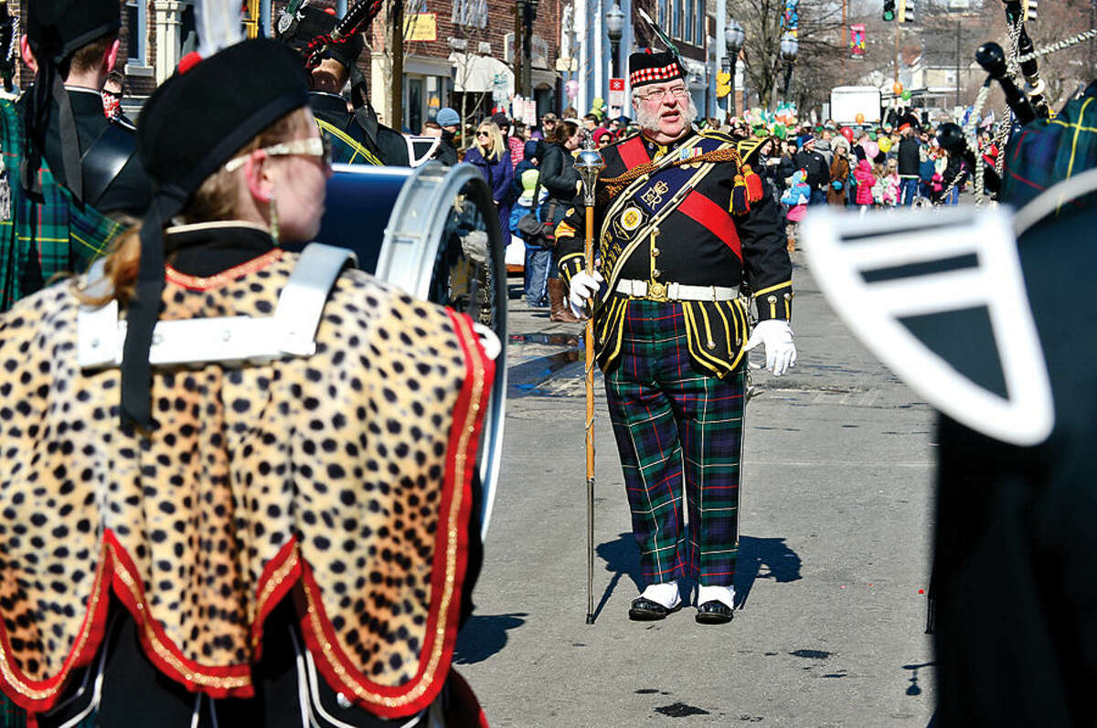 Hour photo / Erik Trautmann Stamford St Patrick's Day Parade participants and local residents including the drum major for the machester Police and Fire Pipe Band enjoy the sunny Saturday afternoon as the procession proceeds down Bedford St.