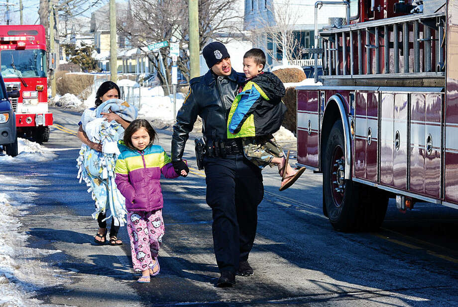 Hour photo / Erik Trautmann A Norwalk police officer evacuates a young family after emergency personnel respond to a fire call at 114 Woodward Ave Saturday morning where a pipe burst realeasing steam into the apartments.