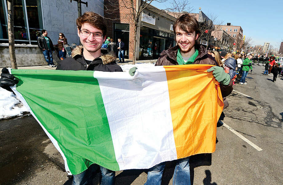 Hour photo / Erik Trautmann Stamford St Patrick's Day Parade participants and local residents including Brian Shaw and Torge Mecker enjoy the sunny Saturday afternoon as the procession proceeds down Bedford St.