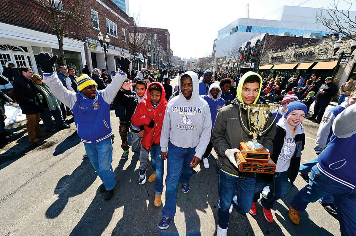 Hour photo / Erik Trautmann Stamford St Patrick's Day Parade participants and local residents including the Cloonan Middle School Bulldogs JV football team enjoy the sunny Saturday afternoon as the procession proceeds down Bedford St.