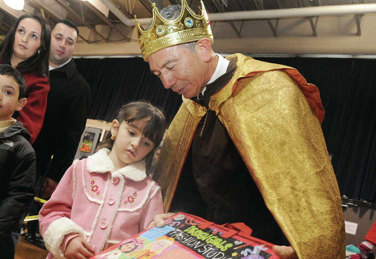 Hour photo/Mattthew Vinci Norwalk police officer Cesar Raminez as one of the three kings gives out donated toys Sunday at St. Joseph Church. Five year old Vivina Ceja was among the many local children to attend the Three Kings celebration.