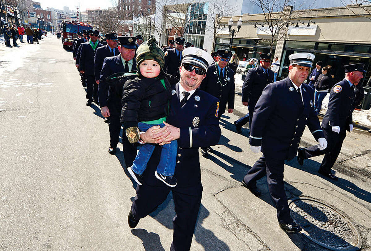 Hour photo / Erik Trautmann Stamford St Patrick's Day Parade participants and local residents including retired Stamford Fire & Rescue Deputy Fire Marshal Ken Bixbee and his grandson Jordan Bixbee, 2, enjoy the sunny Saturday afternoon as the procession proceeds down Bedford St.