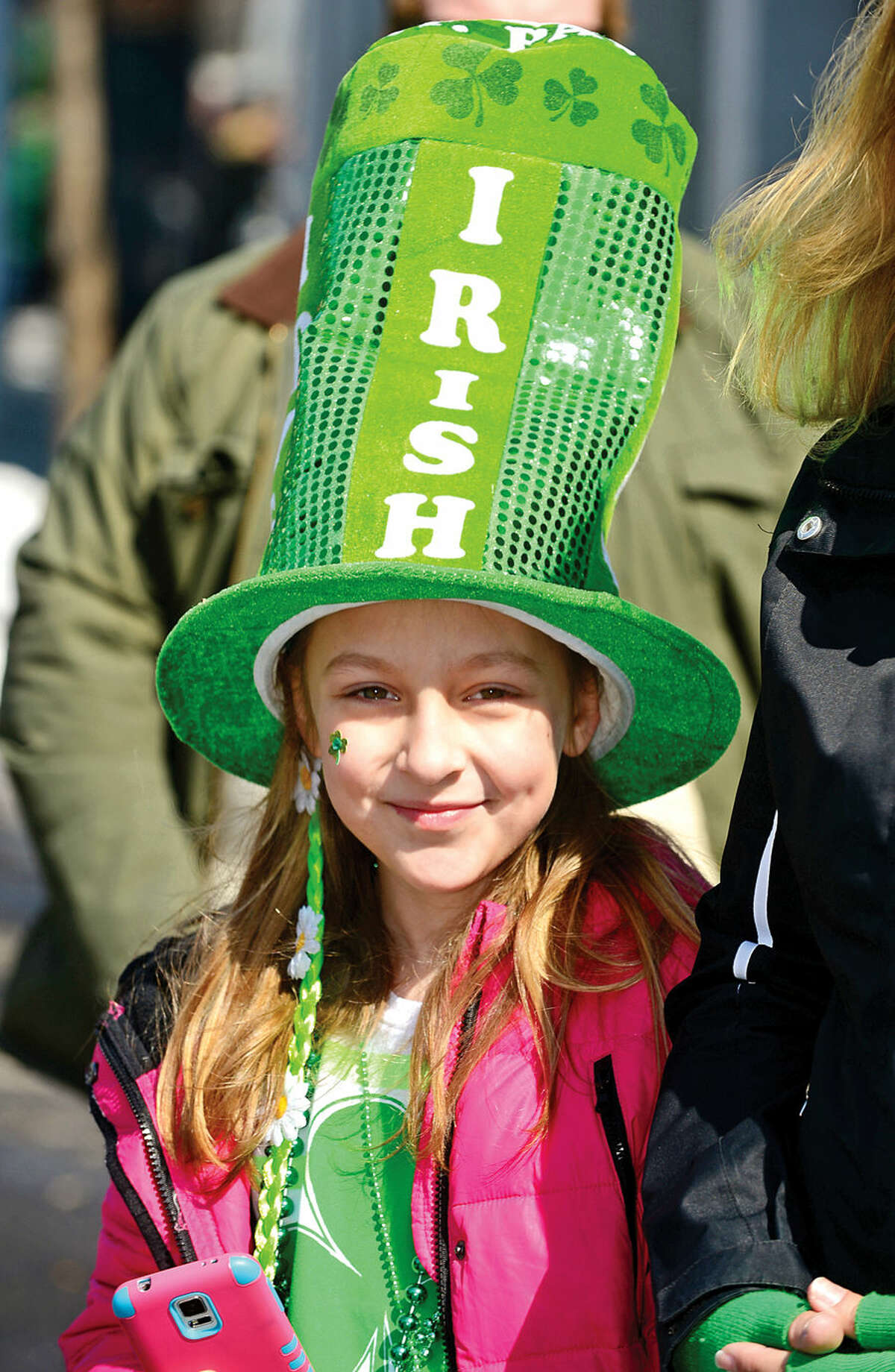 Hour photo / Erik Trautmann Stamford St Patrick's Day Parade participants and local residents including Ashlyn Fllod, 9, enjoy the sunny Saturday afternoon as the procession proceeds down Bedford St.