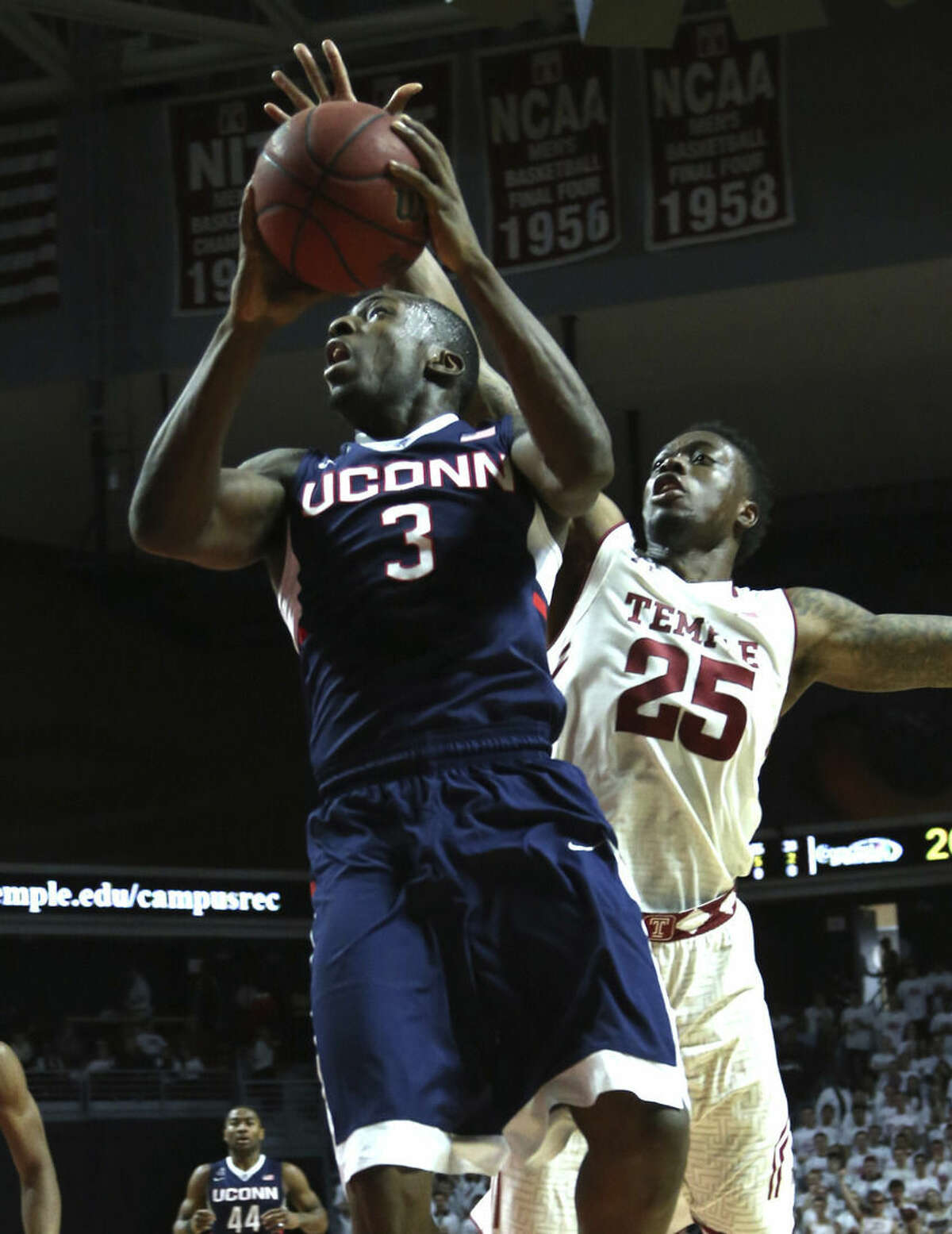 Connecticut guard Terrence Samuel (3) drives to the basket as Temple guard Quenton DeCosey (25) follows in the first half of an NCAA college basketball game, Saturday, March 7, 2015, in Philadelphia. (AP Photo/Laurence Kesterson)