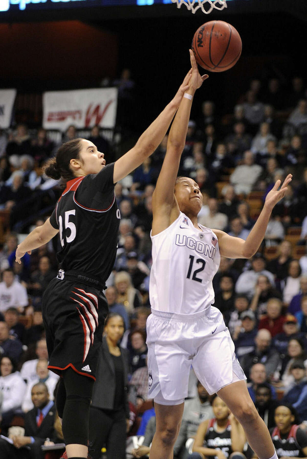 Connecticut's Saniya Chong (12) drives past Cincinnati's Chelsea Jamison (25) during the first half of an NCAA college basketball game in the quarterfinals of the American Athletic Conference tournament in Uncasville, Conn., on Saturday, March 7, 2015. (AP Photo/Fred Beckham)