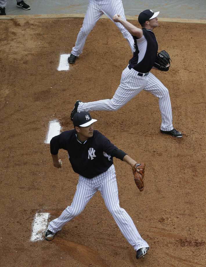 New York Yankees starting pitcher Masahiro Tanaka, of Japan, front, throws in the bullpen with Chase Whitley, rear, during a spring training baseball workout, Saturday, March 7, 2015, in Tampa, Fla. (AP Photo/Lynne Sladky)