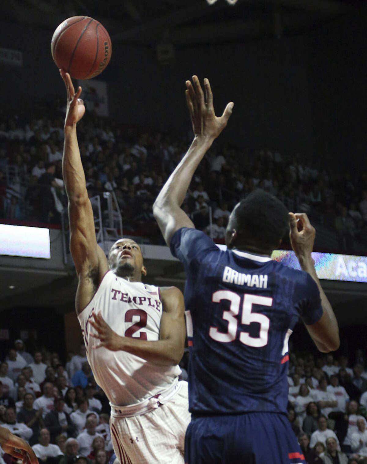 Temple guard Will Cummings (2) takes a shot past Connecticut center Amida Brimah (35) in the second half of an NCAA college basketball game, Saturday, March 7, 2015, in Philadelphia. Temple won 75-63. (AP Photo/Laurence Kesterson)