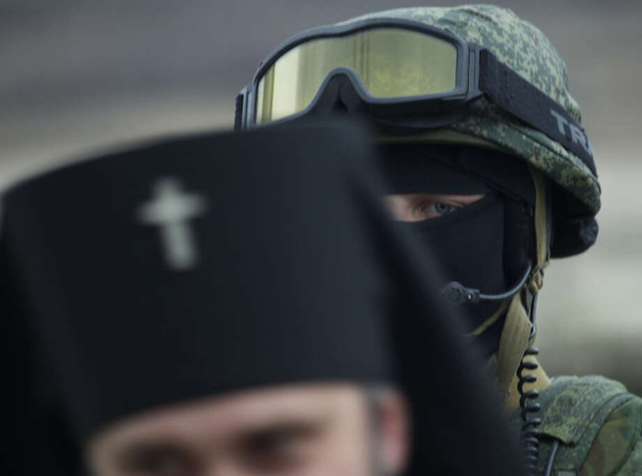 Russian solder is seen behind Ukrainian Orthodox Archbishop Clement, foreground, outside of a Ukrainian military base in the village of Perevalne, outside of Simferopol, Ukraine, on Sunday, March 2, 2014. Hundreds of armed men in trucks and armored vehicles surrounded the Ukrainian military base Sunday in Crimea, blocking its soldiers from leaving. (AP Photo/Ivan Sekretarev)