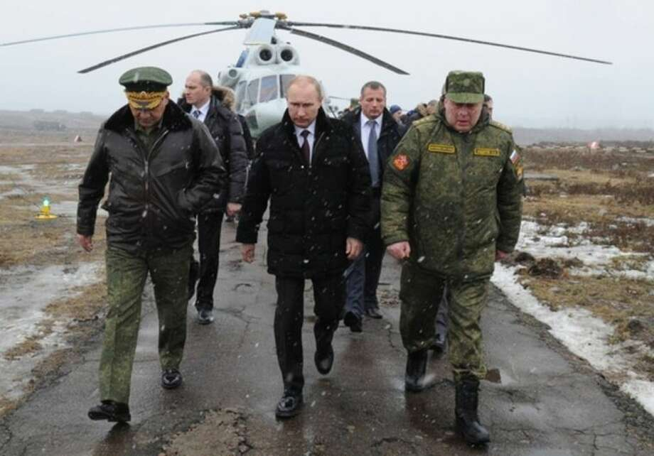 (AP Photo/RIA-Novosti, Mikhail Klimentyev, Presidential Press ServiceRussian President Vladimir Putin, center, and Defense Minister Sergei Shoigu, left, and the commander of the Western Military District Anatoly Sidorov, right, walk upon arrival to watch military exercise near St.Petersburg, Russia, Monday, March 3. Putin has sought and quickly got the Russian parliament's permission to use the Russian military in Ukraine.