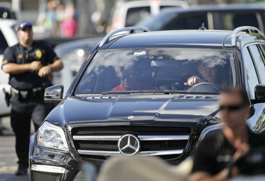 Tiger Woods, in passenger seat, leaves after withdrawing having played 13 holes in the final round of the Honda Classic golf tournament, Sunday, March 2, 2014 in Palm Beach Gardens, Fla. This is the second straight year the No. 1 player in the world didn't finish the Honda Classic. A year ago, it was Rory McIlroy who walked off the course in the middle of the second round. (AP Photo/Wilfredo Lee)