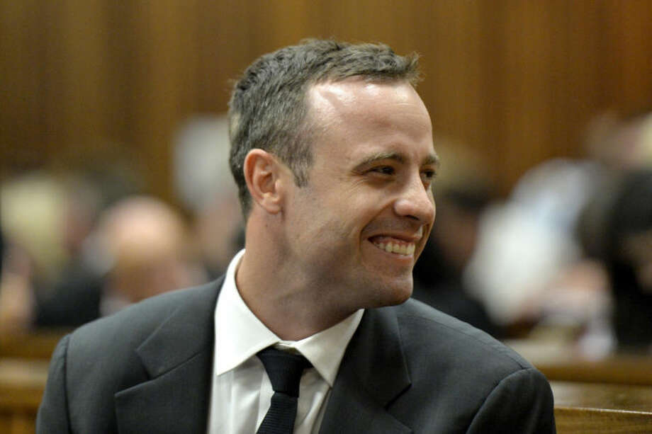 Oscar Pistorius smiles in court during his trial at the high court in Pretoria, South Africa, Monday, March 3, 2014. Pistorius is charged with murder with premeditation in the shooting death of girlfriend Reeva Steenkamp in the pre-dawn hours of Valentine's Day 2013. (AP Photo/Herman Verwey Media24-Pool)