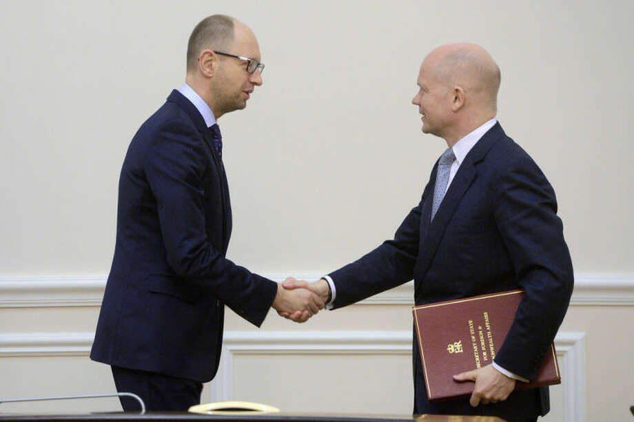 Ukrainian Prime Minister Arseniy Yatsenyuk, left, shakes hands with British Foreign Secretary William Hague in Kiev, Ukraine, Monday, March 3, 2014. Pro-Russian troops took over a ferry terminal on the easternmost tip of Crimea close to Russia on Monday, exacerbating fears that Moscow is planning to bring even more troops into this strategic Black Sea region. (AP Photo/Andrew Kravchenko, Pool)