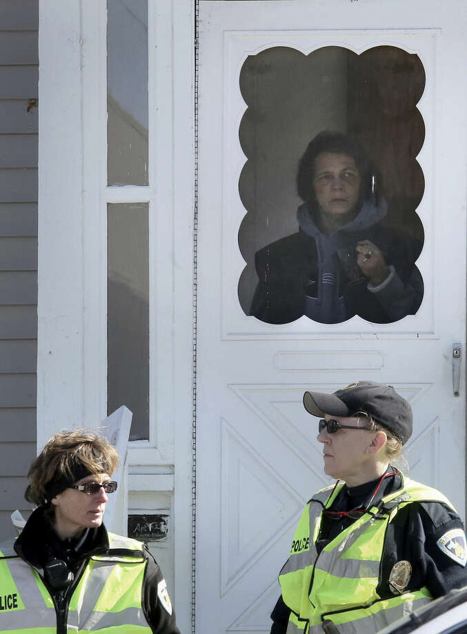 Kathy Bufton, a downstairs resident of the home in which Tony Robinson was killed looks from the front door of the property Saturday, March 7, 2015, in Madison, Wis. Robinson, an unarmed black 19-year-old, was fatally shot Friday by Matt Kenny, a white police officer, the Madison police chief said Saturday, March 7, 2015. (AP Photo/Wisconsin State Journal, John Hart)