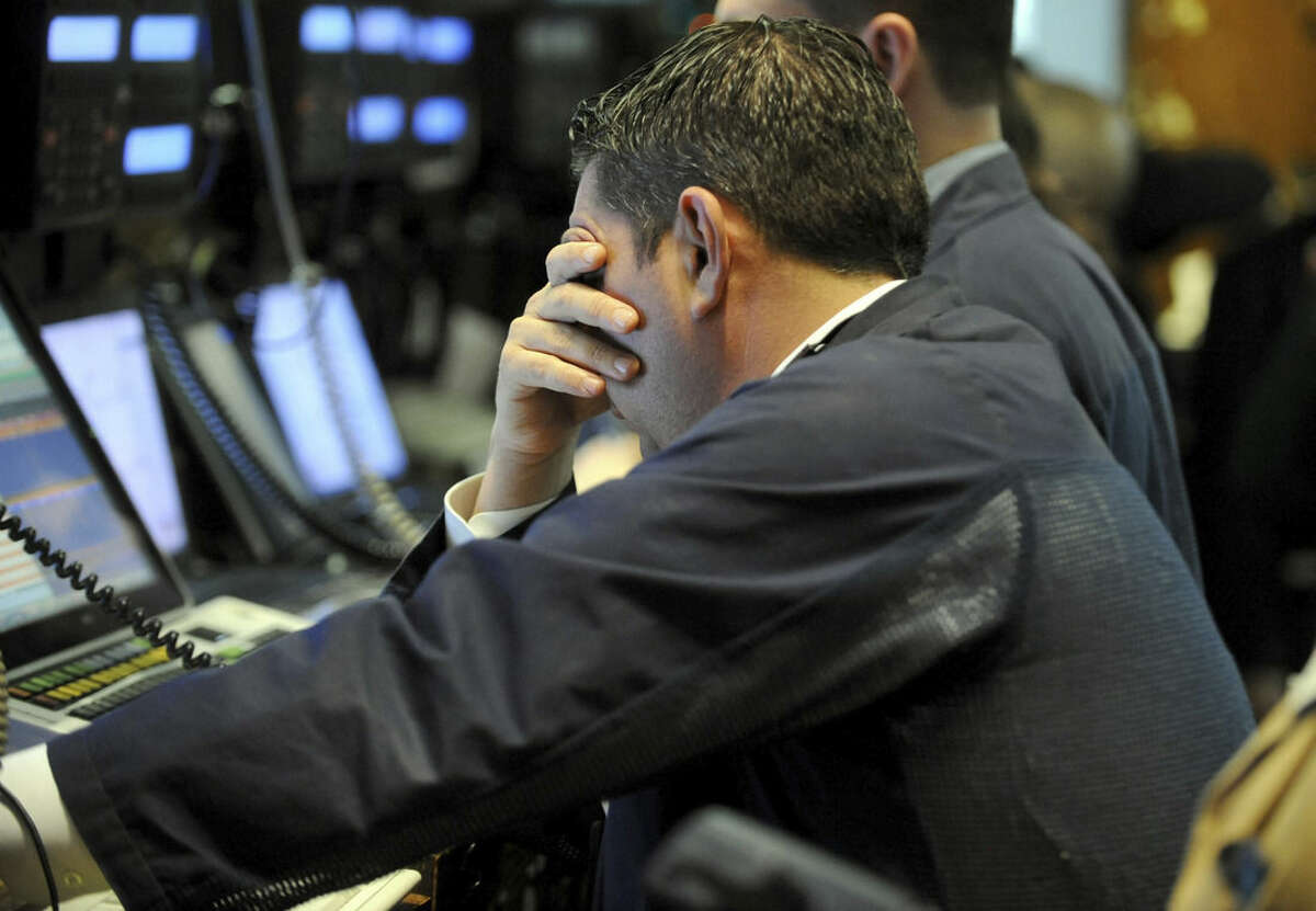 FILE - In this March 9, 2015, file photo, a trader covers his face while working on the floor of the New York Stock Exchange, in New York. The Standard & Poor's 500 index has more than tripled since bottoming out at 676.53 on March 9, 2009. Since that low point, stocks have notched a series of gains without a drop of 20 percent of more. (AP Photo/Henny Ray Abrams, File)