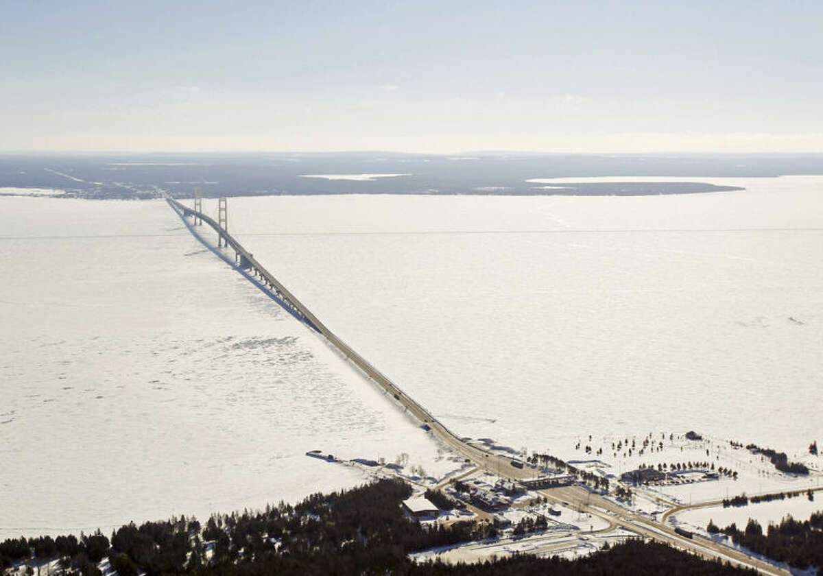 In this Feb. 11, 2014 aerial photo is a view of The Mackinac Bridge which spans a 5-mile-wide freshwater channel that separates Michigan?'s upper and lower peninsulas. The straits is drawing the attention of some who consider the twin 20-inch pipes that stretch across the bottom of the waterway, carrying nearly 23 million gallons of crude oil daily, a symbol of the dangers lurking in the nation?'s sprawling web of buried oil and natural gas pipelines. (AP Photo/ Traverse City Record-Eagle, Keith King, Pool)