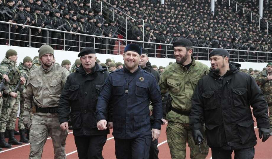 "FILE - In this file photo taken on Monday, Dec. 9, 2015, Chechnya's regional leader Ramzan Kadyrov, center, and other Chechen top commanders inspect Chechen special forces during a a rally at a stadium in Chechen capital Grozny, Russia. Russian President Vladimir Putin bestowed a state award Monday on the leader of Chechnya, the North Caucasus strongman who hailed the suspected killer of an opposition politician as a ""true patriot.""Kadyrov drew criticism Sunday from government opponents after praising Zaur Dadayev, a Chechen suspect in the murder of Kremlin foe Boris Nemtsov. (AP Photo/Musa Sadulayev, file)"