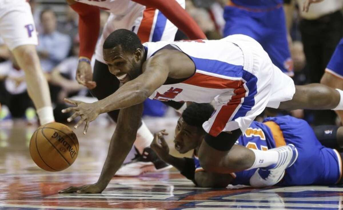 Detroit Pistons guard Rodney Stuckey reaches for the loose ball over New York Knicks guard Iman Shumpert (21) during the first half of an NBA basketball game in Auburn Hills, Mich., Monday, March 3, 2014. (AP Photo/Carlos Osorio)