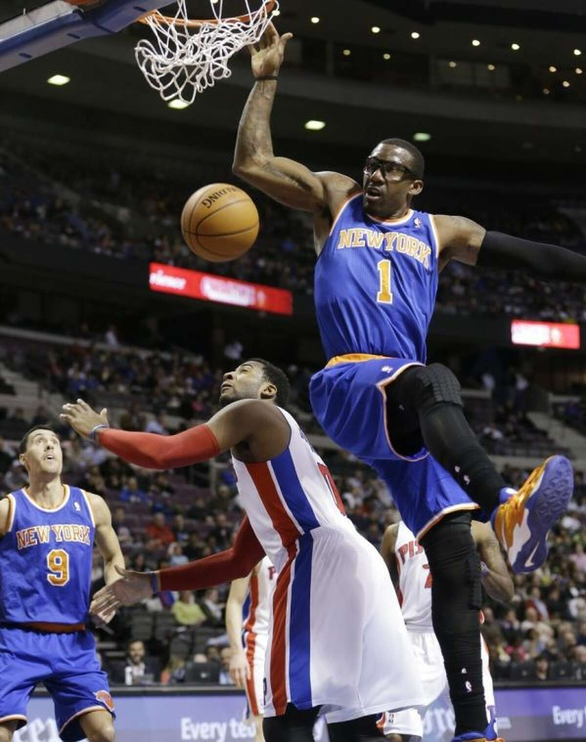 New York Knicks forward Amar'e Stoudemire (1) dunks on Detroit Pistons center Andre Drummond (0) during the first half of an NBA basketball game in Auburn Hills, Mich., Monday, March 3, 2014. (AP Photo/Carlos Osorio)