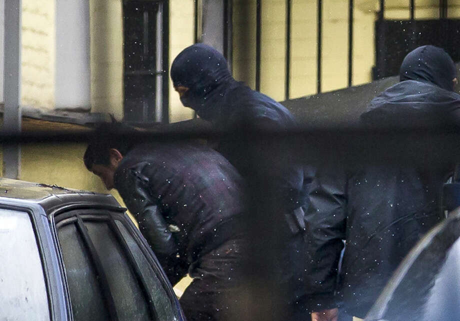 Police escorts Zaur Dadaev, believed to be one of five suspects in the killing of Boris Nemtsov, into a court room in Moscow, Russia, March 8, 2015. Five suspects in the killing of prominent Russian opposition figure Boris Nemtsov have been delivered to the court for arraignment, the spokeswoman for a Moscow court said Sunday. The statement by Anna Fedeeva to reporters outside the courthouse came one day after the Federal Security service said two suspects had been detained. Russian news agencies late Saturday reported that two others had been detained, and Investigative Committee spokesman Vladimir Markin said Sunday there was a fifth suspect. Details remain vague in the case despite President Vladimir Putin's pledge to pursue the killers vigorously. (AP Photo/Ivan Sekretarev)