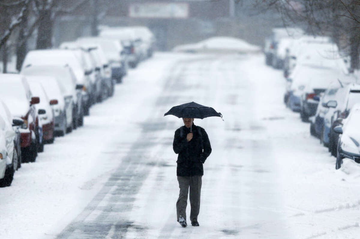 A morning commuter walks to a train station during a winter snowstorm Monday, March 3, 2014, in Philadelphia. Spring is in sight, but winter kept its icy hold on much of the country Monday, with up to a foot of snow and plummeting temperatures expected across the Mid-Atlantic states and up the East Coast. (AP Photo/Matt Rourke)